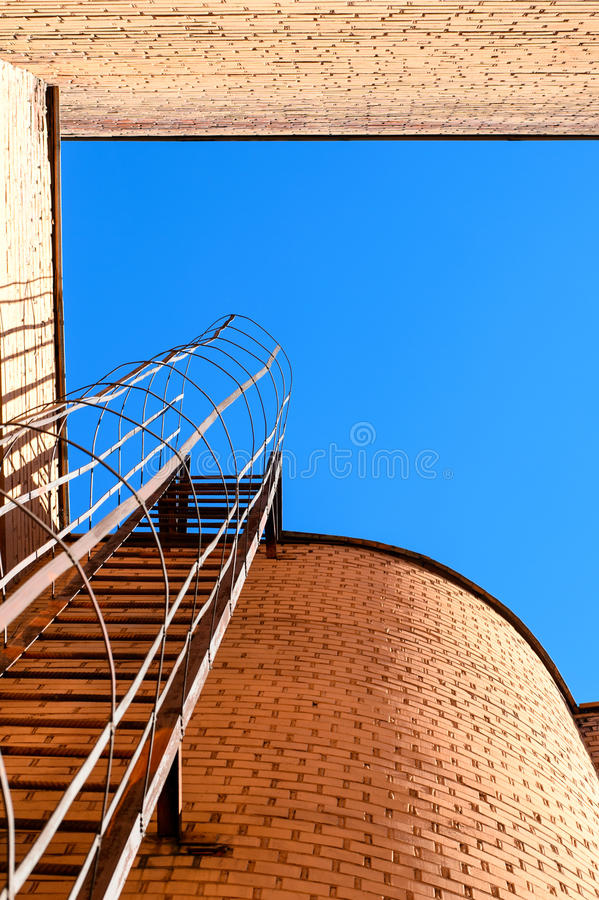 Industrial ladder, blue sky and brick walls of the building stock images