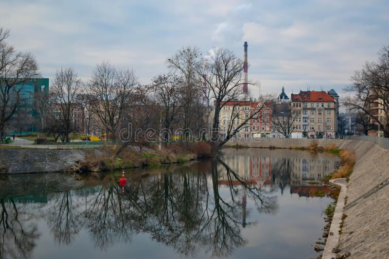 Industrial landscape in the city of Wroclaw with buildings and a chimney of an industry. And a river stock photos