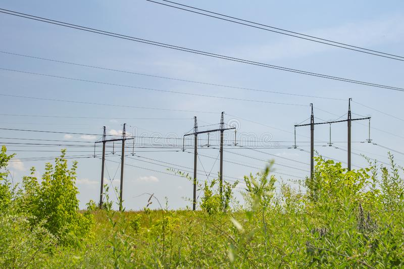 Industrial landscape - high-voltage power transmission line against a blue sky royalty free stock photo