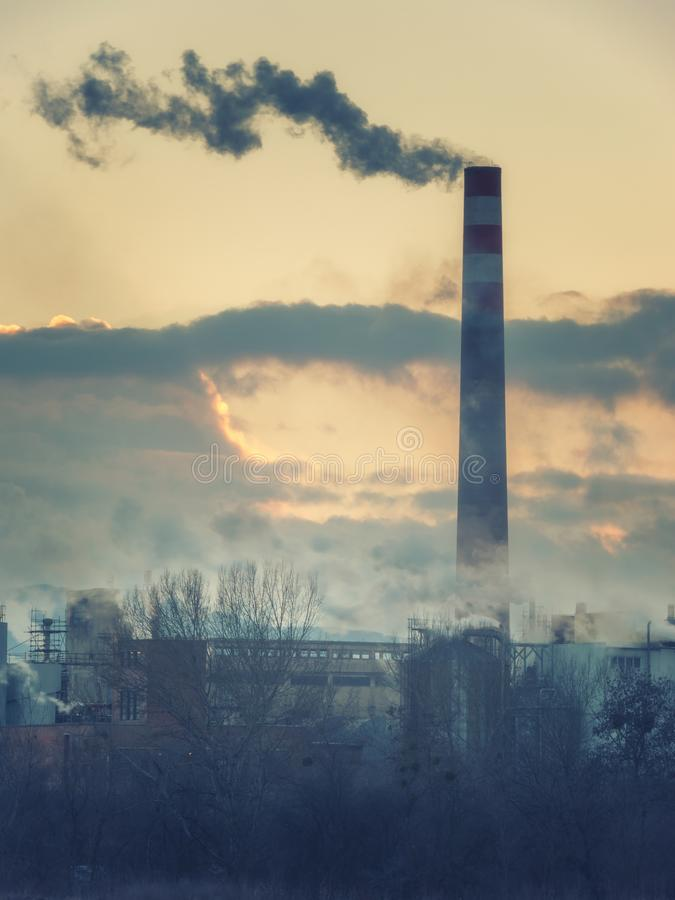 Industrial landscape, plant with smoke in sunset light, air pollution royalty free stock image