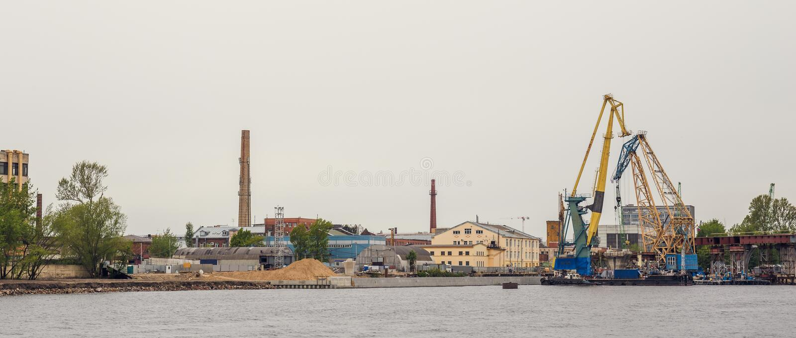 Industrial landscape with port and cargo cranes on river, shipping, trade and international logistic stock images