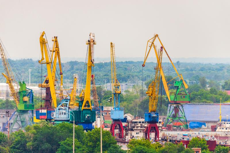 Industrial landscape with port cranes of yellow and blue colors in the port on the background of the city view. Cargo, container, discharge, dock, export royalty free stock images