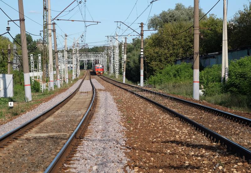 Industrial landscape railroad track rails and passenger train moving on sunny summer day. Industrial landscape with two way railroad track rails and red royalty free stock images