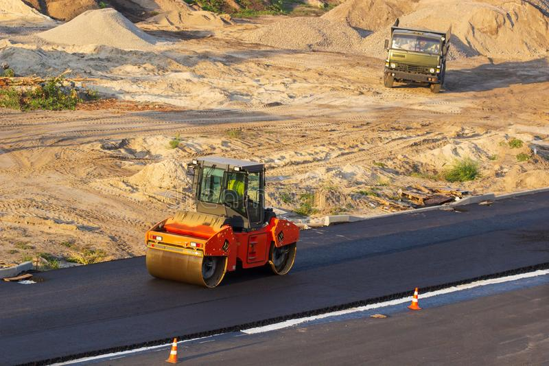 Industrial landscape with rollers that rolls a new asphalt on the road. Repair work, complicated transport movement. Industrial landscape with rollers that stock photo