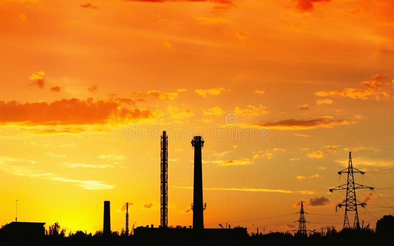 Industrial landscape with silhouettes of pipes and towers against the fiery orange sunset sky. royalty free stock photo