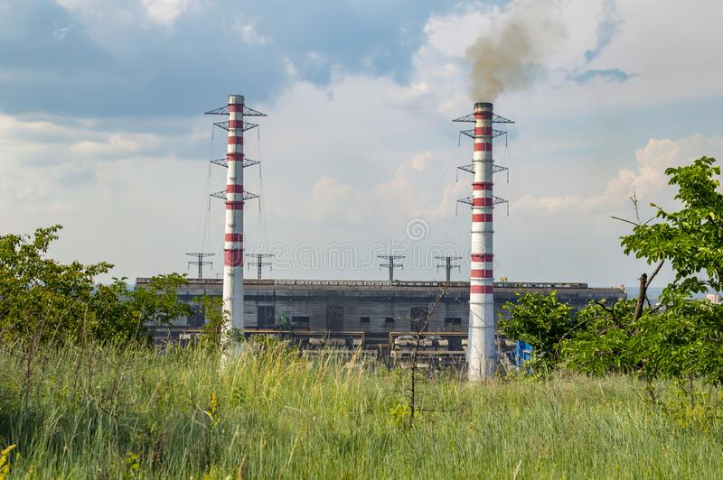 Industrial landscape - smoking chimneys of a thermal power plant against a blue sky royalty free stock image