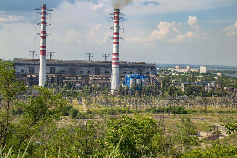 Industrial landscape - smoking chimneys of a thermal power plant against a blue sky. Industrial landscape - smoking chimneys of a thermal power plant against the royalty free stock images