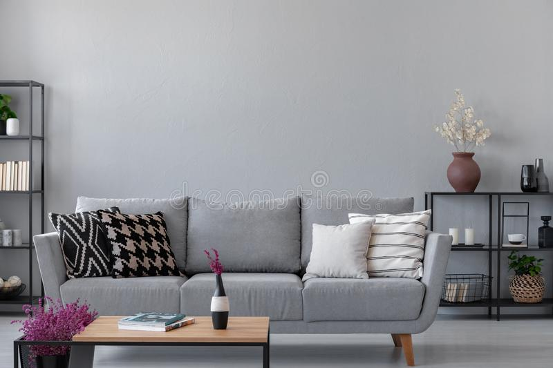 Industrial living room with simple grey sofa with copy space on the wall. Industrial living room with simple grey sofa and metal furniture, real photo with copy royalty free stock image