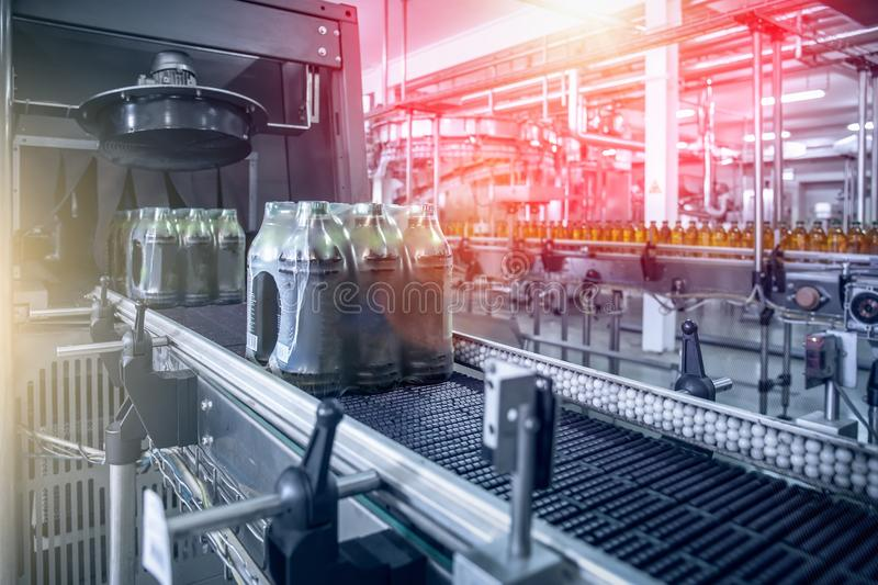 Industrial machine for packaging of beverage plastic bottles at plant or factory, blue toned as abstract industry background stock image
