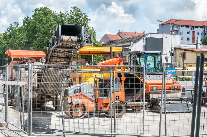 Industrial machinery for asphalt pavement work on the street construction and reconstruction site surrounded with metal safety fen. Ce royalty free stock photo