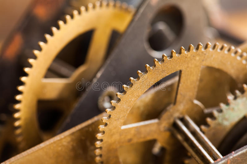 Industrial machinery bronze cog transmission macro view. Aged metal gear wheel teeth mechanism, shallow depth field. Selective focus stock images