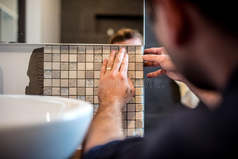 Industrial man worker applying mosaic tiles in bathroom walls stock photos
