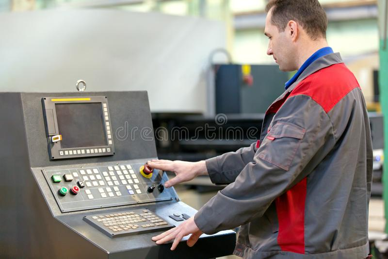 Industrial man worker operating workshop machine. Manufacture industrial worker operating coordinate punching sheet cutting machine in workshop royalty free stock photo