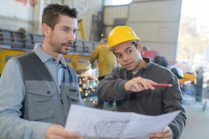 Industrial manager and worker showing machine. Factory stock photo