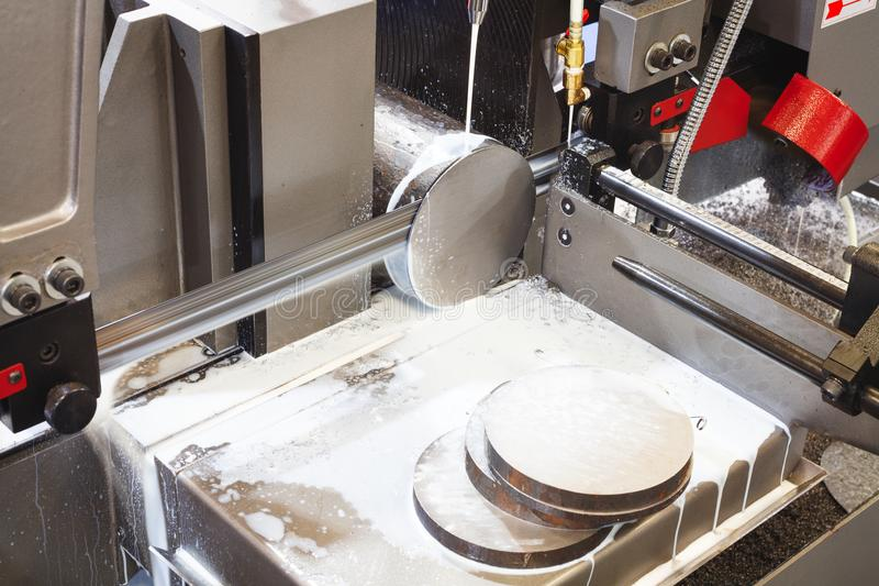 Industrial metal machining cutting process of blank detail by mechanical electrical saw. stock photos