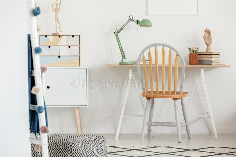 Industrial mint colored lamp on stylish wooden desk in white kid`s bedroom stock photography