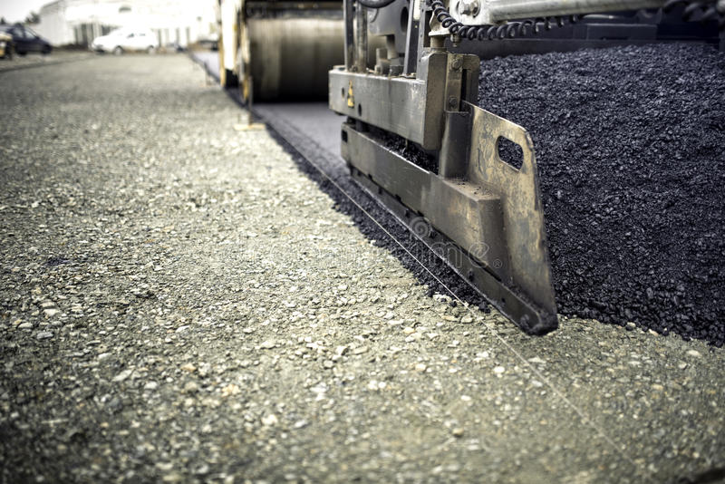 Industrial pavement truck laying fresh asphalt, bitumen during road works. Construction of highways stock images