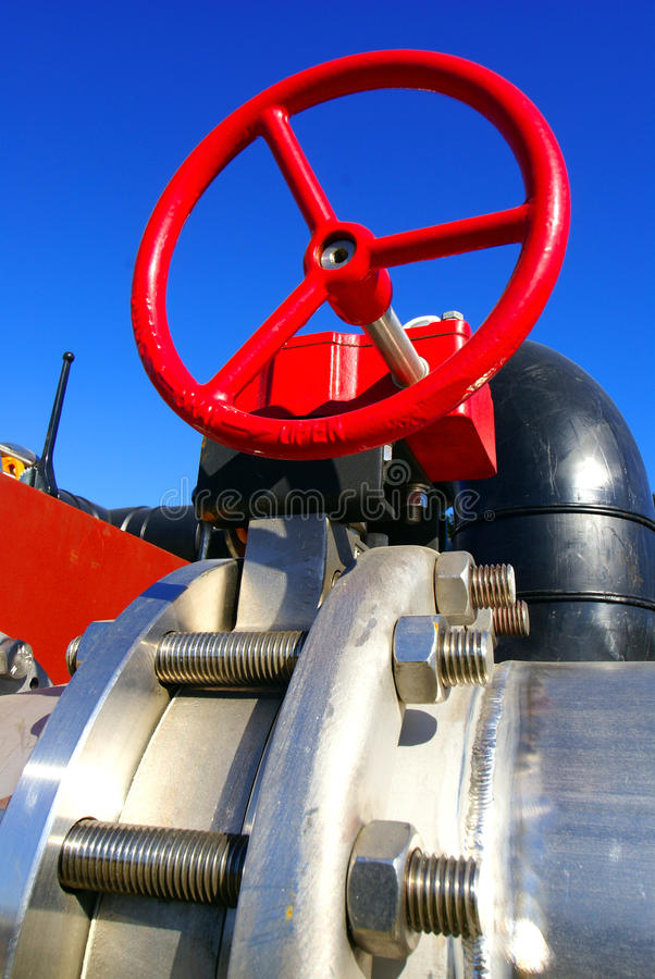 Industrial pipelines against blue sky. Industrial pipelines with red wheel against blue sky stock images