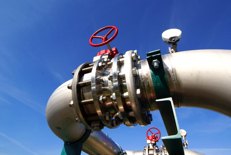 Industrial pipelines against blue sky. Industrial pipelines and valves with red wheels against blue sky stock photography