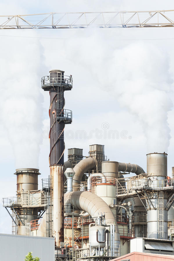 Industrial plant of a furniture factory with smoking smokestacks. Industrial plant of a furniture factory with smoking smokestack,tube,silos royalty free stock photos