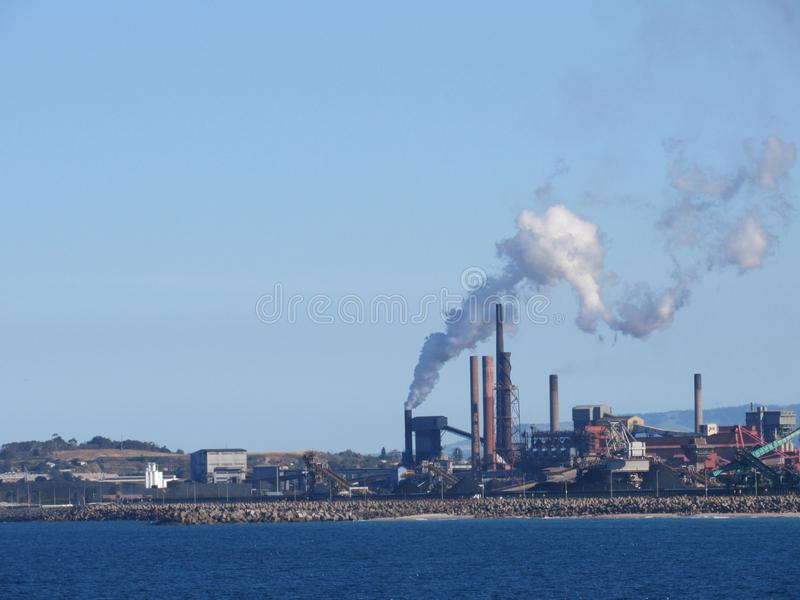 Industrial plants are emitting smoke. background is the sky and the front is the sea. Industrial plants are emitting smoke. background is the blue sky and the royalty free stock photos