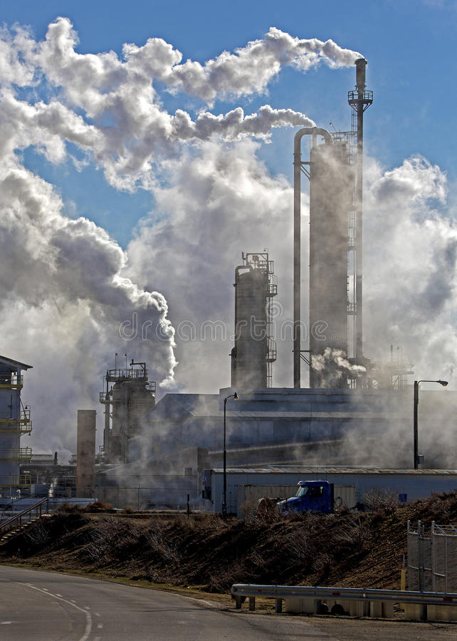 Industrial pollution. Smoke and steam belch out of smokestacks at an industrial plant royalty free stock photos
