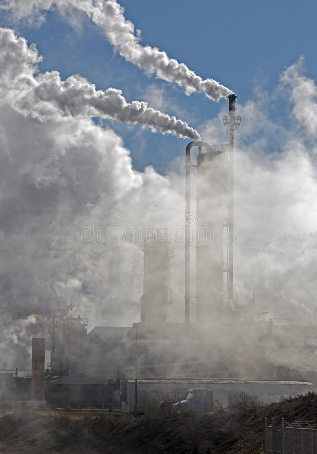 Industrial pollution. Smoke and steam belch out of smokestacks at an industrial plant stock photo
