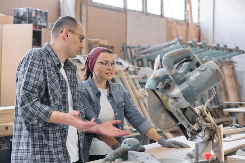 Industrial portrait of two working men and woman, talking at machine tools stock photo