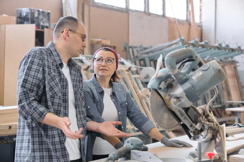 Industrial portrait of two working men and woman, talking at machine tools stock photography