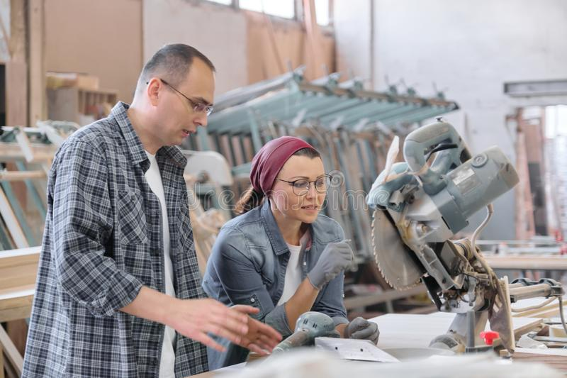 Industrial portrait of working men and women, people talking at work, furniture joinery production stock images