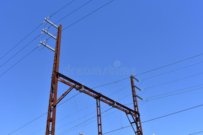 Industrial power lines against blue sky stock photos