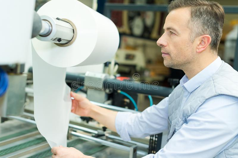 Industrial printing press worker looking at rolled paper royalty free stock image
