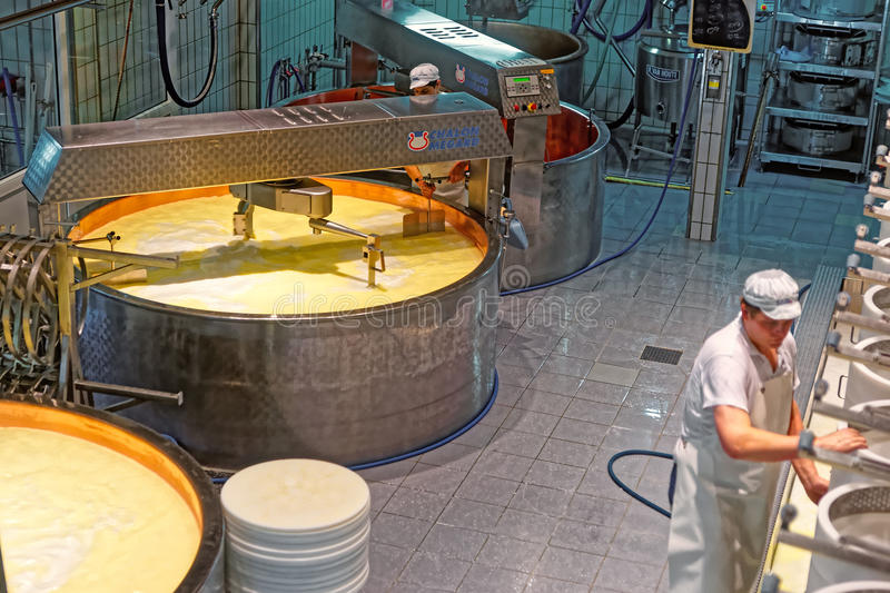 During industrial production of Gruyere cheese. GRUYERE, SWITZERLAND - DECEMBER 31, 2014: During industrial production of Gruyere cheese at the cheese making stock photography