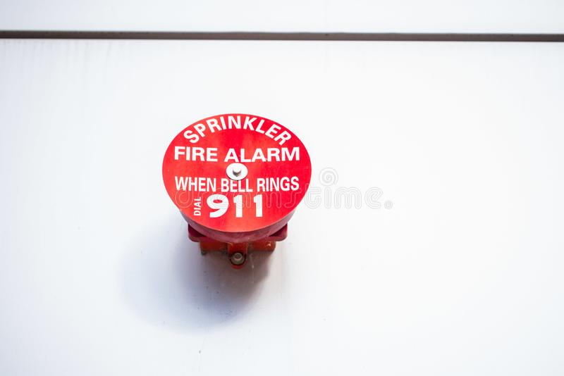 Industrial red fire alarm system. 911 industrial fire sprinkler red alarm on the white wall of the factory royalty free stock image