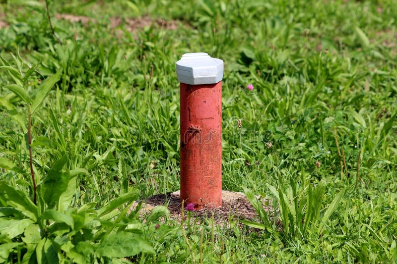 Industrial red partially rusted pipe covered with white metal cap on hard concrete foundation surrounded with uncut green grass stock image