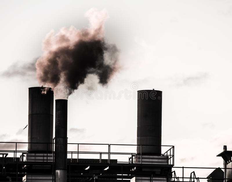 Industrial Revolution. Old industrial site polluting the air with dark smoke royalty free stock image