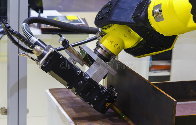 Industrial robot performs an operation of cutting metal stock image