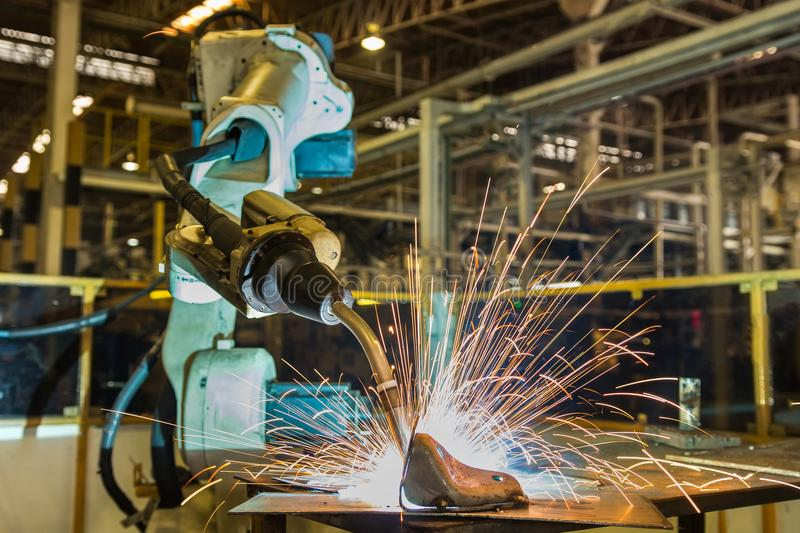 Industrial robot is welding automotive part in factory royalty free stock photography