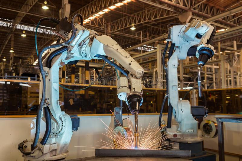 Industrial robot is welding assembly automotive part in factory. Industrial robot is welding assembly automotive part in car factory stock image
