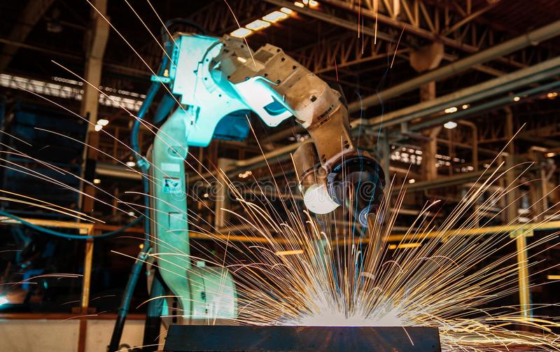 Industrial robot is welding in automotive part factory. Industrial robot is welding in automotive part in car factory royalty free stock image