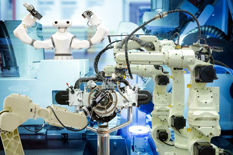 Industrial robotics teamwork working with engine parts on smart factory stock photo