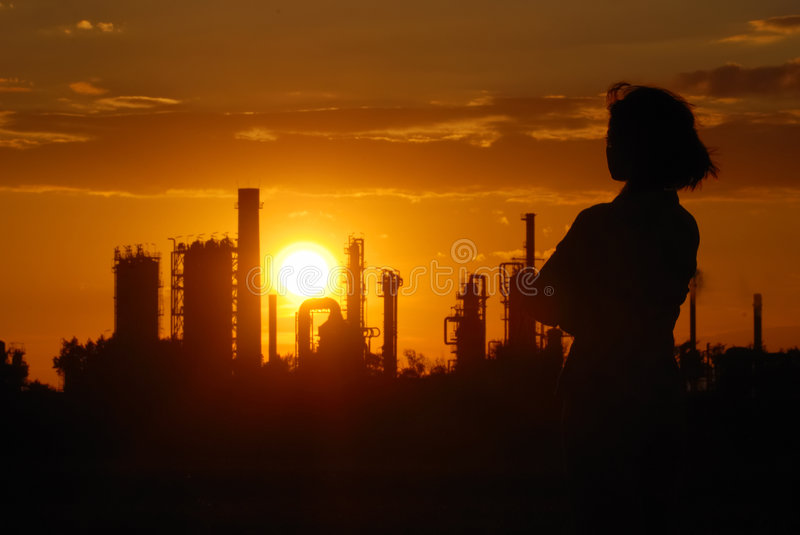 Industrial romantic - oil refinery sunset. Woman looks on oil refinery at sunset (silhouette royalty free stock image