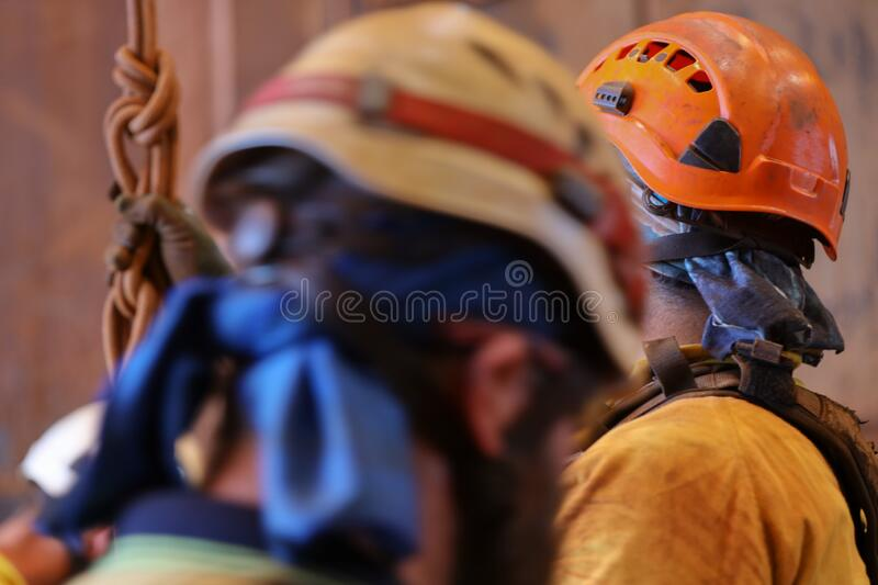 Industrial rope access construction worker wearing orange helmet fall safety head protection royalty free stock images