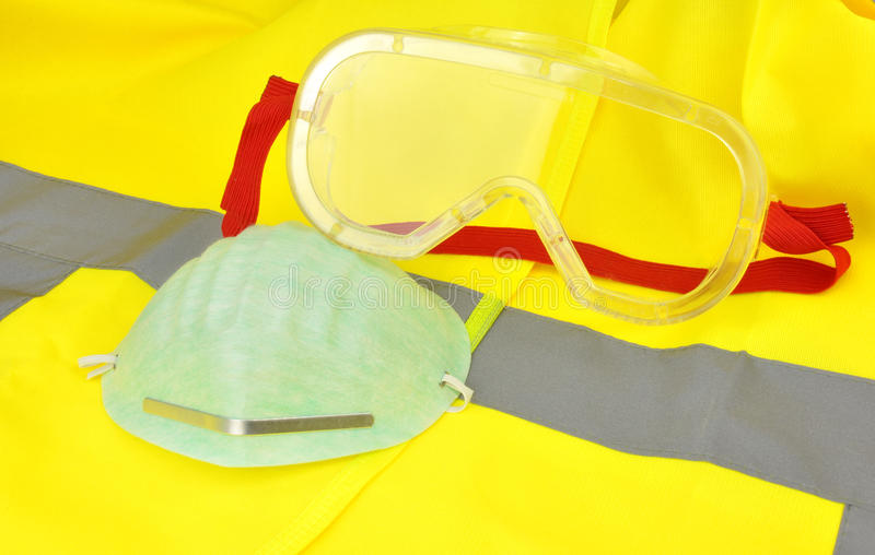 Industrial Safety Goggles. Plastic industrial safety goggles with red elastic strap on a yellow high visibility vest stock image
