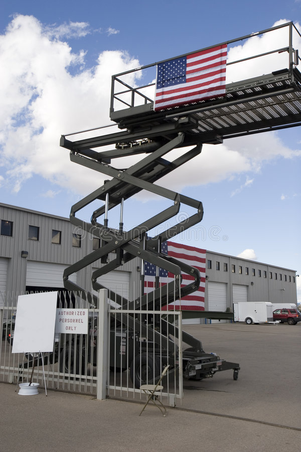 Industrial scissor lift. An industrial scissor lift with american flag stock photos