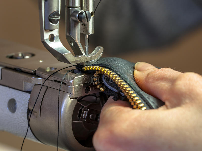 Industrial Sewing machine operated in workshop. Industrial Sewing machine in action in workshop operated with hands working on garment stock photo