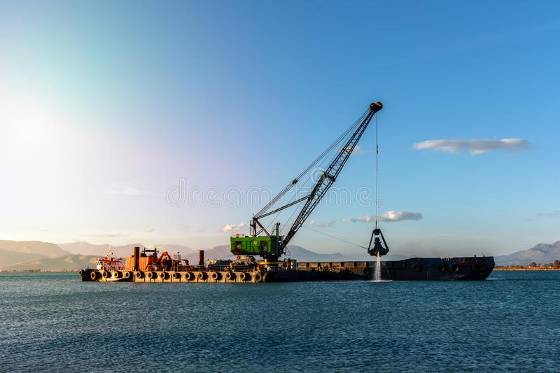 Industrial ship that digs sand. Making harbor deeper for bigger ships to be able to dock royalty free stock photography