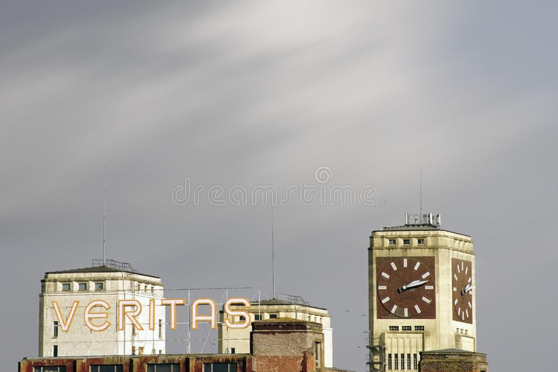 Industrial site Veritas Wittenberge. Wittenberge, Germany - February 25, 2015: The top of the clock tower and the logo of an industrial building of the former royalty free stock photography