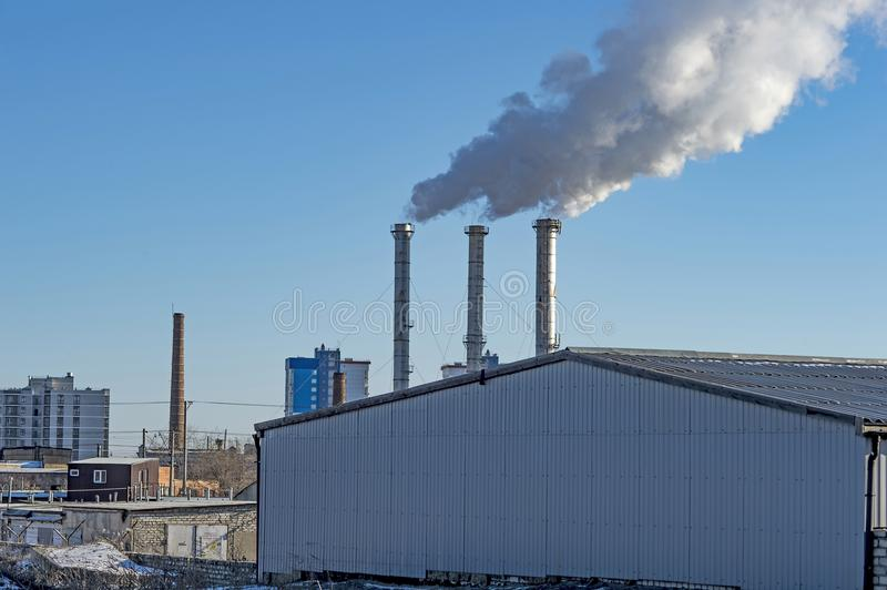 Industrial smoke from chimney on blue sky. royalty free stock image