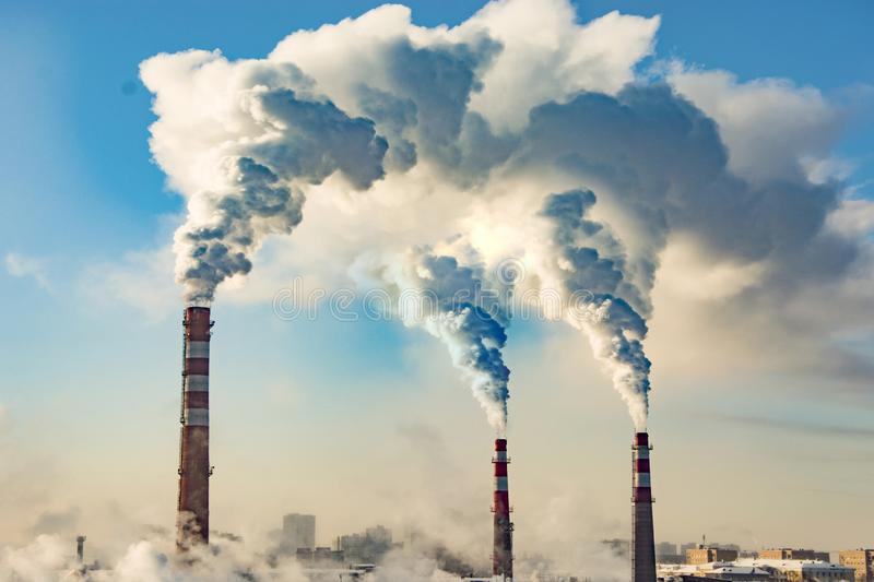 Industrial smokestacks against the blue sky . royalty free stock photo